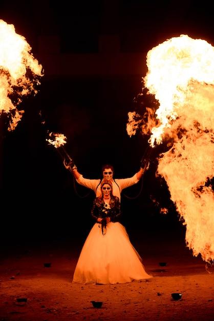 Couple d'halloween debout avec le lance-flammes. grand feu Photo Premium