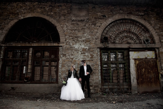 Couple d'halloween. vêtu de vêtements de mariage zombie romantique Photo Premium