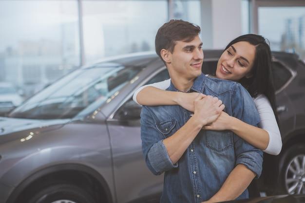 Couple heureux achète une voiture neuve chez un concessionnaire Photo Premium