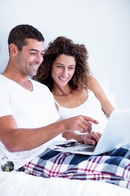 Couple heureux à l'aide d'un ordinateur portable sur le lit Photo Premium