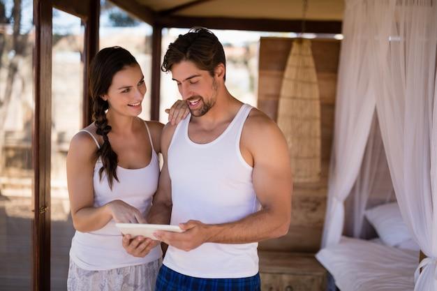 Couple heureux à l'aide de tablette numérique dans le chalet Photo gratuit