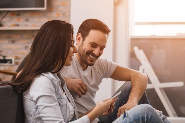 Couple Heureux, Appréciant Le Contenu Multimédia Dans Un Téléphone Intelligent, Assis Sur Le Sol Photo Premium