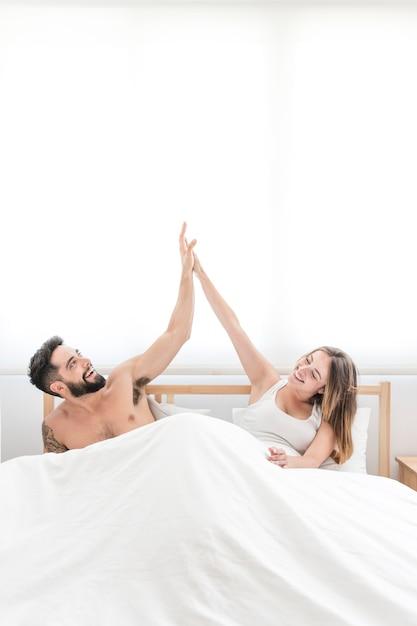Couple heureux assis sur le lit donnant cinq haut Photo gratuit