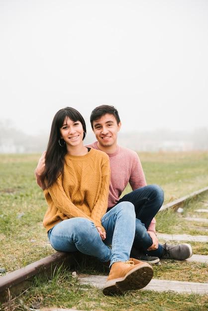 Couple heureux assis sur des rails Photo gratuit