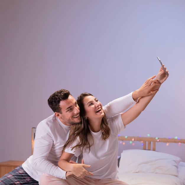 Couple heureux au lit prenant selfie Photo gratuit
