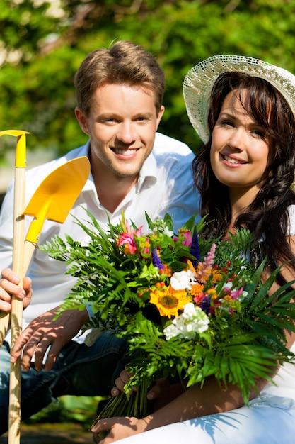 Couple heureux avec bouquet de fleurs et outils de jardinage Photo Premium