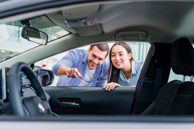 Couple heureux chez un concessionnaire automobile Photo gratuit