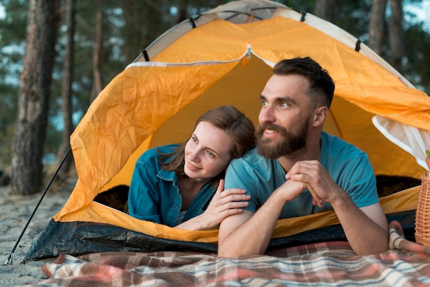 Couple heureux couché dans la tente Photo gratuit