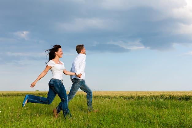 Couple heureux en cours d'exécution sur un pré Photo Premium