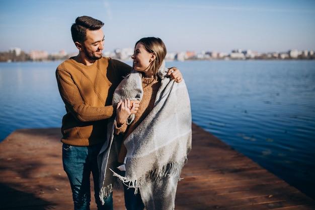 Couple heureux avec couverture au bord de la rivière Photo gratuit
