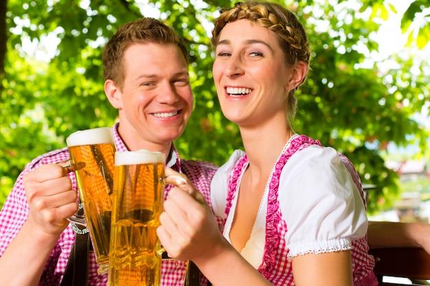 Couple heureux dans le café en plein air, boire de la bière Photo Premium