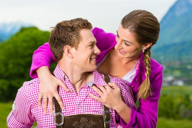 Couple heureux dans une prairie alpine en tracht Photo Premium