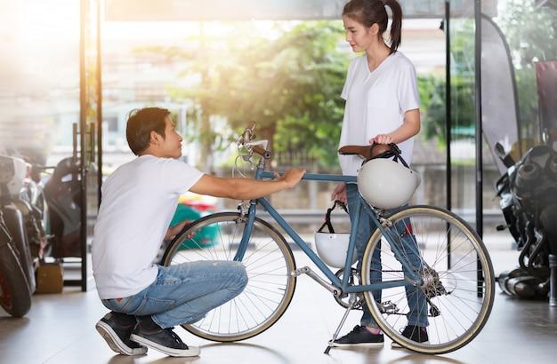 Couple heureux debout et vérifiant le vélo à la maison avant de voyager Photo Premium