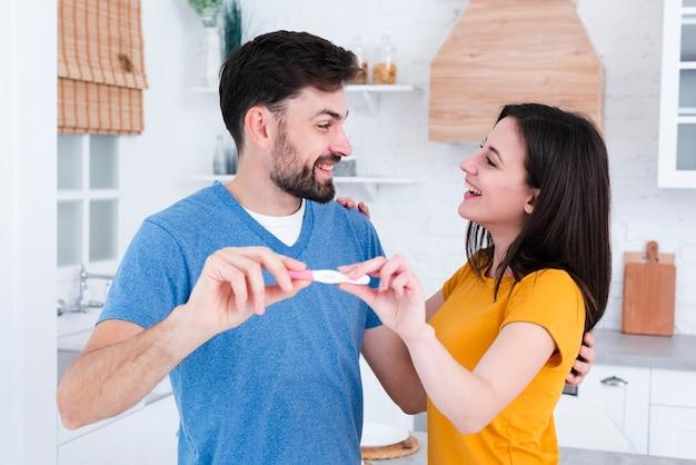 Couple heureux exhibant un test de grossesse Photo gratuit