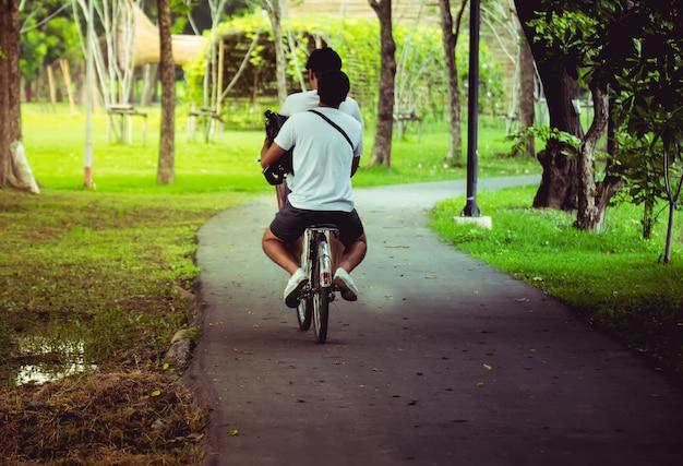 Couple heureux fait du vélo dans le parc. Photo Premium