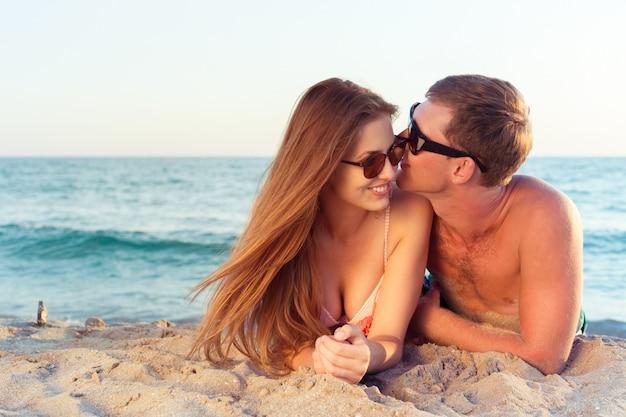 Couple heureux en lunettes de soleil s'amuser sur la plage Photo Premium