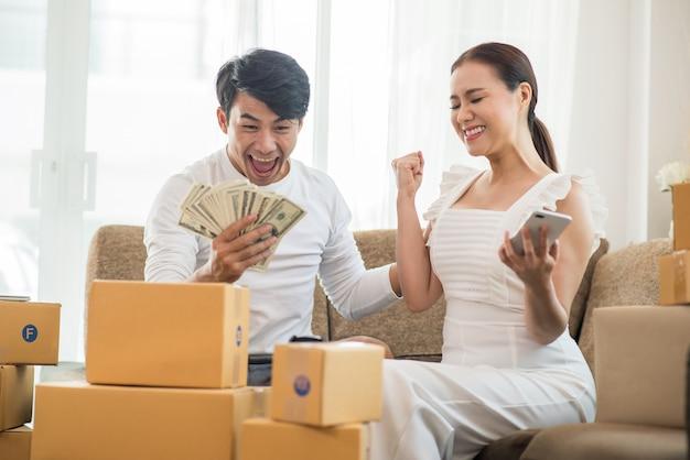 Couple heureux à la maison avec les affaires en ligne, marketing en ligne et travail indépendant Photo gratuit