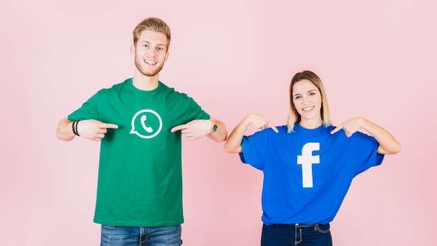 Couple heureux pointant sur leur t-shirt avec facebook et icône whatsapp Photo gratuit