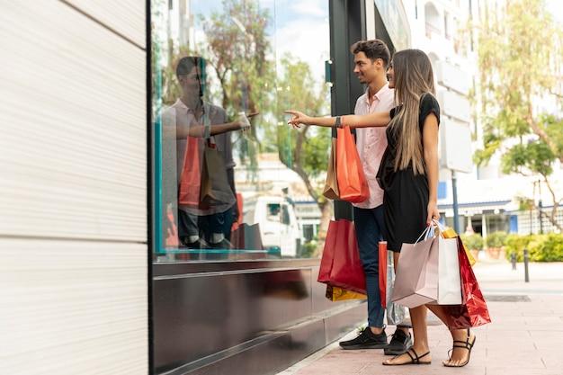 Couple heureux près d'un magasin à la recherche de ventes Photo gratuit