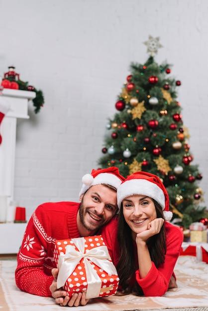 Couple heureux près de sapin de noël Photo gratuit