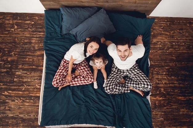 Un couple heureux en pyjama est assis sur le lit avec une petite fille. Photo Premium