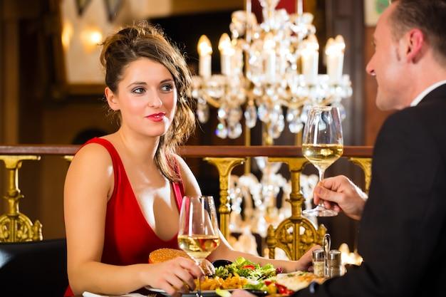 Couple heureux a un rendez-vous romantique, un restaurant raffiné, un grand lustre Photo Premium