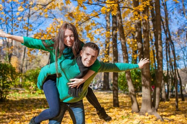 Couple heureux s'amuser dans le parc de l'automne par une journée ensoleillée d'automne Photo Premium