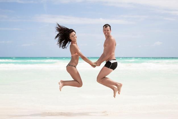 Couple heureux de sauter sur la plage Photo gratuit