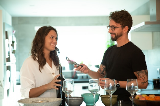 Couple Heureux, Servir, Dîner, Et, Ouverture, Bouteille Vin Photo gratuit