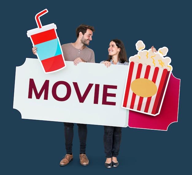 Couple heureux tenant des icônes de film Photo gratuit