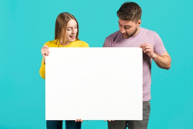 Couple heureux tenant une pancarte blanche Photo gratuit