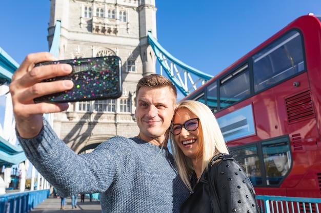 Couple heureux touristes prenant selfie à tower bridge à londres Photo Premium
