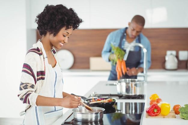 Couple heureux en train de préparer un repas dans la cuisine Photo Premium