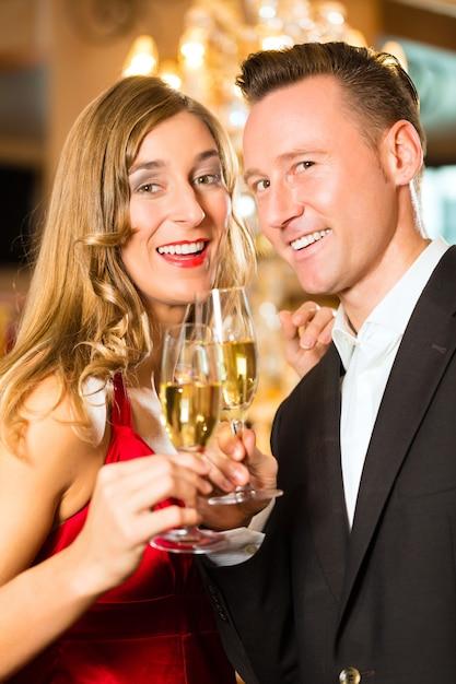 Couple, homme et femme, buvant du champagne dans un restaurant gastronomique, chacun tenant un verre de vin mousseux à la main Photo Premium
