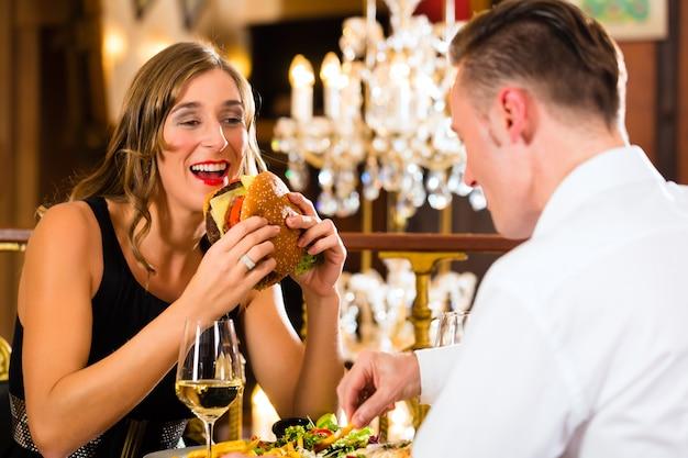 Couple, homme et femme un restaurant gastronomique ils mangent fast food, burger et frites Photo Premium