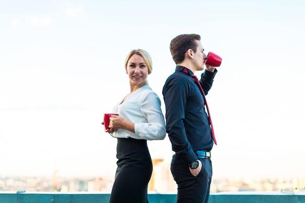 Couple d'hommes d'affaires, bel homme brune et jolie femme blonde se tiennent sur le toit et boivent du café Photo Premium