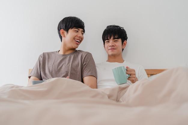 Couple d'hommes homosexuels asiatiques parlant d'avoir un bon moment à la maison moderne. jeune amant asiatique mâle heureux se détendre reste boire un café après le réveil en position couchée sur un lit dans la chambre à la maison à la maison le matin. Photo gratuit