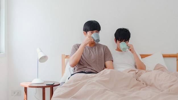 Couple d'hommes homosexuels asiatiques parlant d'avoir un bon moment à la maison moderne. jeune amant de l'asie, lgbtq + mâle heureux, détente, repos, boisson, café après le réveil, allongé sur le lit dans la chambre à la maison du matin. Photo gratuit
