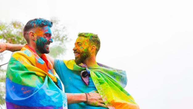 Couple homosexuel avec des visages peints rire et embrasser Photo gratuit