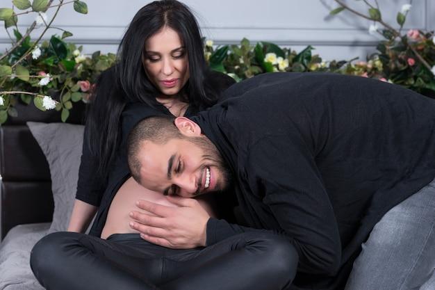 Couple International Amoureux, Homme écoutant Le Ventre De Sa Femme Enceinte Alors Qu'il était Assis Sur Le Lit Douillet Gris Dans La Chambre Photo Premium