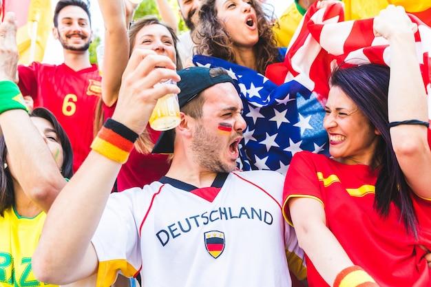 Un couple international de supporters célébrant ensemble au stade lors d'un match Photo Premium