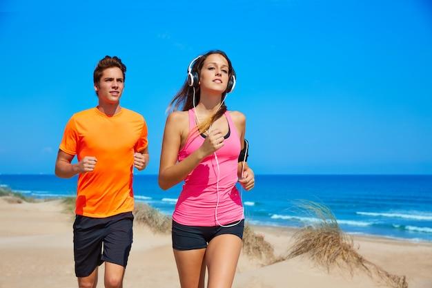 Couple jeune en cours d'exécution sur la plage en été Photo Premium
