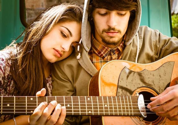 Couple de jeunes adolescents amoureux de la guitare Photo Premium