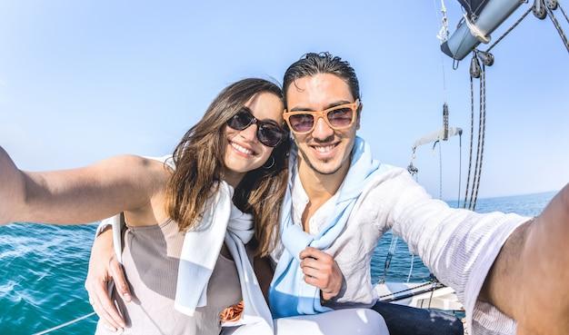 Couple de jeunes amoureux prenant selfie en bateau à voile autour du monde Photo Premium