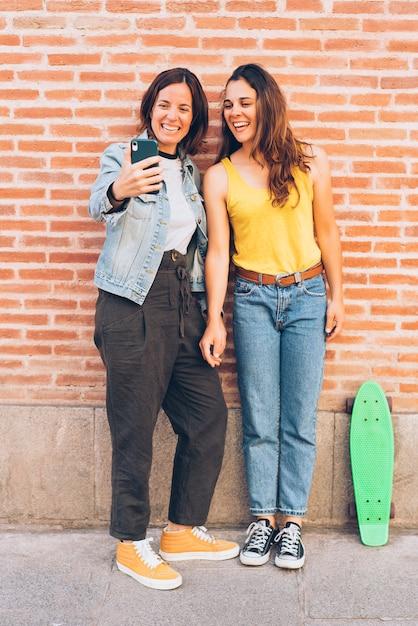 Couple de jeunes femmes faisant un selfie dans un mur de briques. Photo Premium