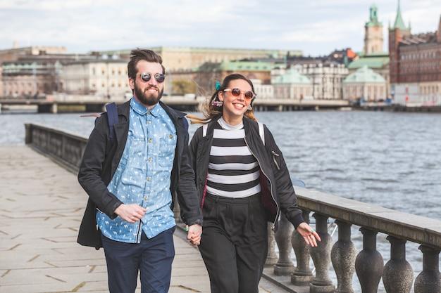 Couple de jeunes hipster courir main dans la main à stockholm Photo Premium