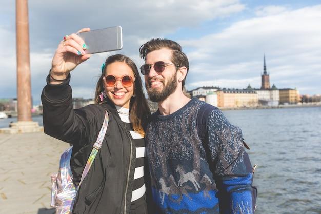 Couple de jeunes hipster prenant un selfie à stockholm Photo Premium