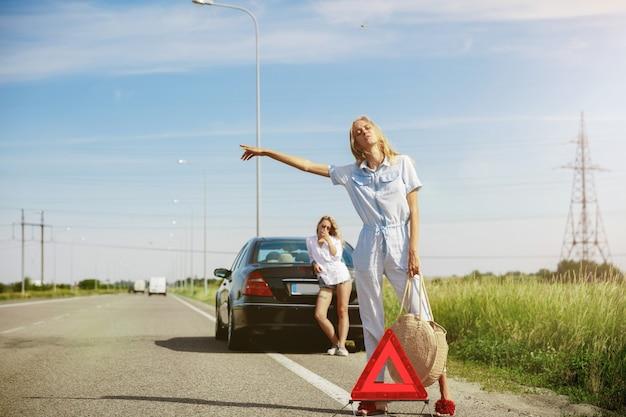 Couple De Jeunes Lesbiennes En Voyage De Vacances Sur La Voiture En Journée Ensoleillée Photo gratuit