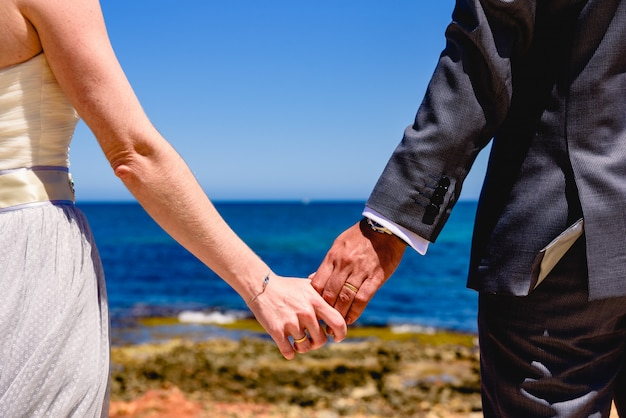 Couple de jeunes mariés amoureux de leur dos, mains regardant la mer. Photo Premium