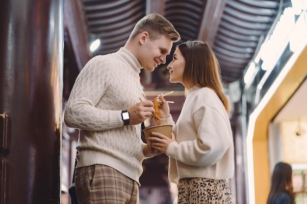 Couple De Jeunes Mariés Manger Des Nouilles Avec Des Baguettes à Shanghai à L'extérieur D'un Marché Alimentaire Photo gratuit